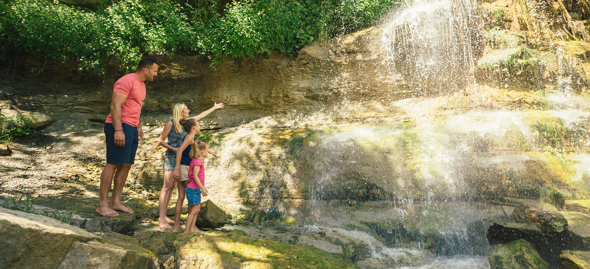 Family standing underneath a waterfall